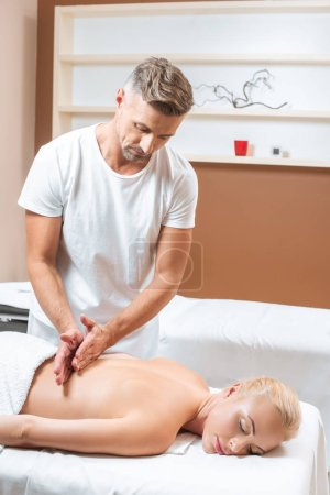 Photo for Handsome masseur doing back massage in spa room - Royalty Free Image