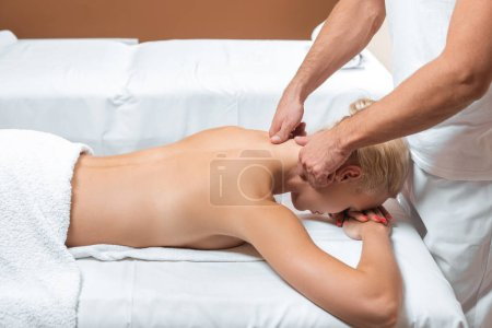Photo for Male therapist doing neck massage to woman in beauty salon - Royalty Free Image