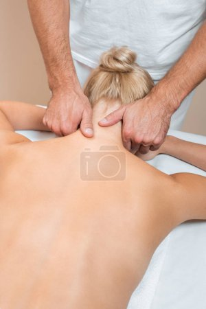 Photo pour Masseur masculin faisant massage du cou dans le salon de spa - image libre de droit