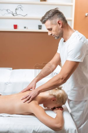 Handsome masseur doing massage of back to blonde woman