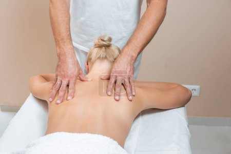 Photo for Male masseur doing back massage to woman in spa room - Royalty Free Image