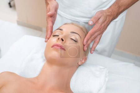 Male masseur doing massage to woman in spa room