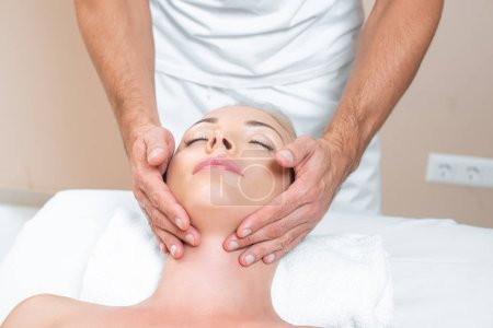 Photo pour Masculin thérapeute faire massage du visage à la femme dans le salon de beauté - image libre de droit