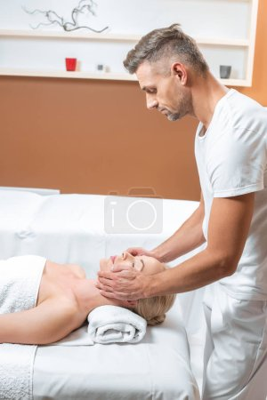 Photo for Male masseur doing face massage in spa salon - Royalty Free Image