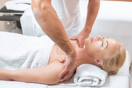 Male masseur doing shoulder massage to woman in spa salon