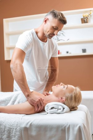 Handsome therapist doing shoulder massage in spa salon