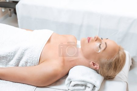 Beautiful woman lying with eye patches in spa