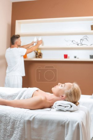 Photo for Masseur taking bottles from shelf while woman lying on massage table - Royalty Free Image