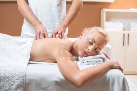 Photo pour Femme blonde, couché avec les yeux fermés tandis que l'homme fait massage - image libre de droit