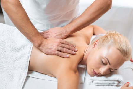 Photo for Male masseur doing back massage to attractive woman in spa - Royalty Free Image