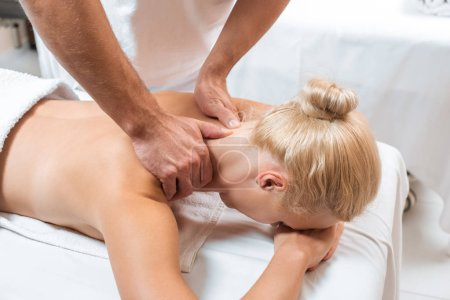 Photo for Male masseur doing neck massage to blonde woman in spa - Royalty Free Image