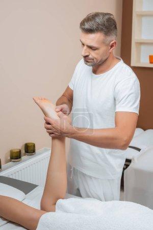 handsome masseur massaging woman foot in spa