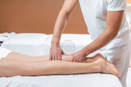 cropped view of man massaging woman legs in spa