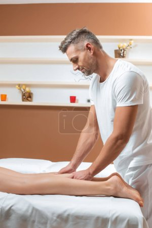 Photo for Adult handsome man massaging woman legs in spa - Royalty Free Image