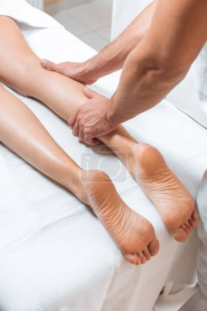 cropped view of man massaging woman legs on white massage table