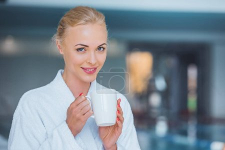 smiling attractive blonde woman holding white cup in spa