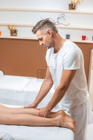 Photo for Handsome man massaging woman legs on white massage table - Royalty Free Image