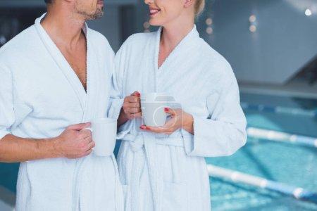 Photo pour Vue recadrée gai homme / femme debout près d'une piscine avec tasses - image libre de droit