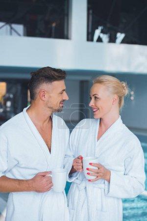 Photo pour Couple souriant en peignoirs, debout près d'une piscine avec tasses - image libre de droit
