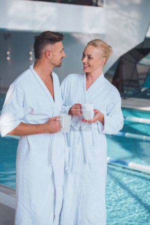 smiling couple in white bathrobes standing near swimming pool and holding cups