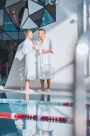 Photo for Couple in white bathrobes standing near swimming pool with beverages - Royalty Free Image