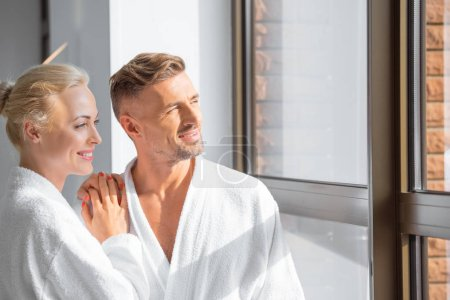 cheerful adult couple hugging and looking at window in spa