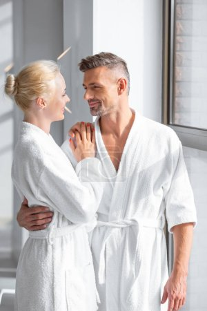 smiling couple standing near window and hugging in spa