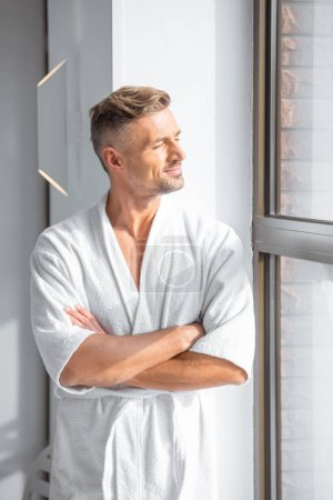 handsome man in white bathrobe with arms crossed looking at window