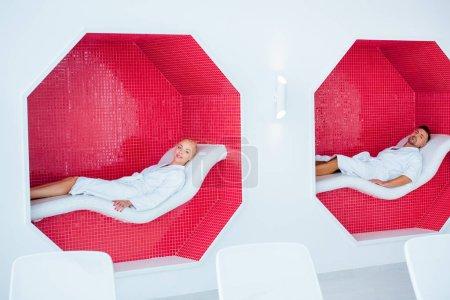 Photo pour Couple adulte allongé sur les transats dans octogones de mosaïque en spa - image libre de droit