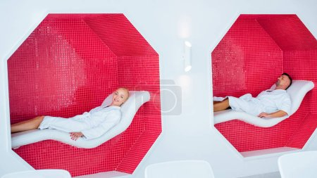 blonde woman and handsome man in white bathrobes resting on deck chairs in mosaic octagons