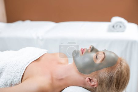 beautiful blonde woman lying with facial clay mask in spa