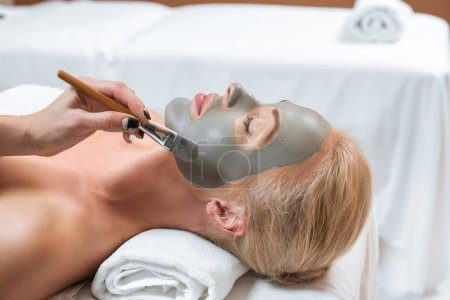 close up of beautician applying clay mask with brush on woman face