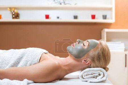 blonde woman lying on table with clay mask on face in spa