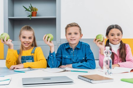 cheerful classmates rejoicing with green apples in hands after lesson