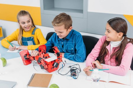smiling classmates making a robot at STEM robotics class