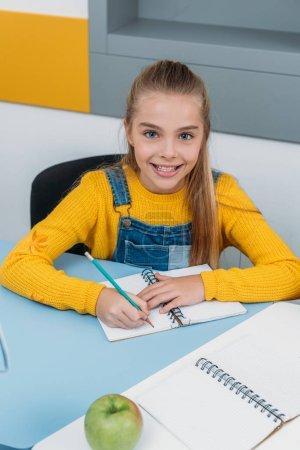 Photo pour Heureux enfant écrit dans un bloc-notes pendant le cours avec pomme sur le bureau - image libre de droit