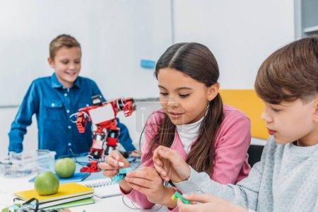 camarades de classe heureux faire un robot au cours de la leçon de robotique de tige