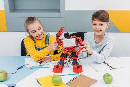 Photo for Happy classmates presenting robot during STEM robotics lesson - Royalty Free Image