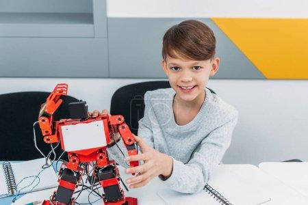 Photo pour Écolier travaillant avec robot à la leçon de robotique STIM - image libre de droit