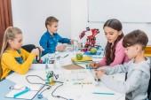 attentive schoolchildren working on robot at STEM robotics lesson