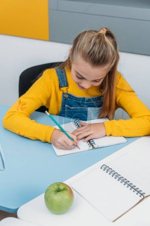 schoolkid writing in notepad during class