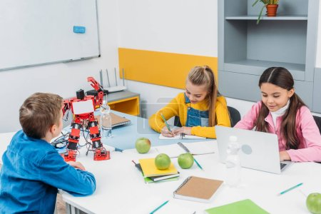 Photo for Schoolchildren writing and using laptop at STEM robotics lesson - Royalty Free Image