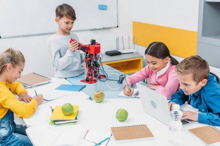 Photo for Schoolchildren writing, using laptop, working on robot at STEM robotics lesson - Royalty Free Image