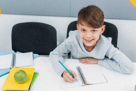 happy schoolboy writing in notepad in classroom