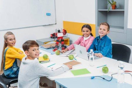 joyful children looking at camera at STEM robotics lesson