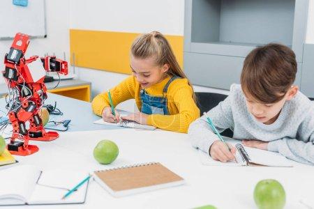 attentive children writing at STEM robotics lesson