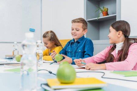 happy children sitting at desk in classroom