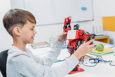 smiling schoolboy playing with red handmade robot in classroom