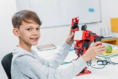 smiling schoolboy looking at camera and holding red handmade robot in classroom