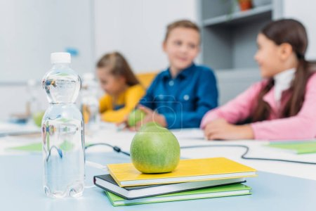 green ripe apple on notebooks and schoolchildren at background in classroom